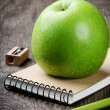 Green apple and school supplies — Stock Photo