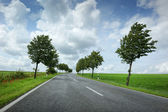 Road with cloudy sky — Stock Photo