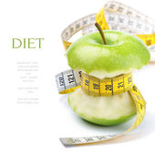 Green apple core and measuring tape. Diet concept — Stockfoto