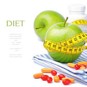 Green apples, vitamins and measuring tape — Stock Photo