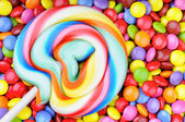 Striped lollipop and multicolored smarties — Stock Photo