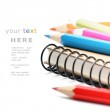 Colorful pencils and notebook isolated over white — Stock Photo #12728075