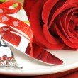 Red rose and cutlery on white plate — Stock Photo #12727601
