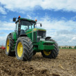 Green tractor in plowed field — 图库照片
