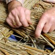 Man's hands making a wicker chair - Stock Photo