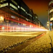Urban city road with car light trails at night - Stock Photo