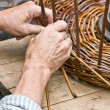 Man's hands making a wicker basket - Stock Photo