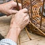 Man's hands making a wicker basket — Stock Photo