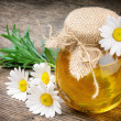 Glass pot of honey with daisies - Stock Photo
