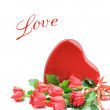 Red roses with heart shaped box of chocolate - Stock Photo