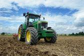 Green tractor in plowed field — Stock Photo