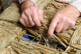 Man's hands making a wicker chair — Stock Photo