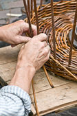 Man's hands making a wicker basket — Stock Photo