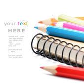 Kolorowe kredki i notebook na białym tle nad białym — Zdjęcie stockowe
