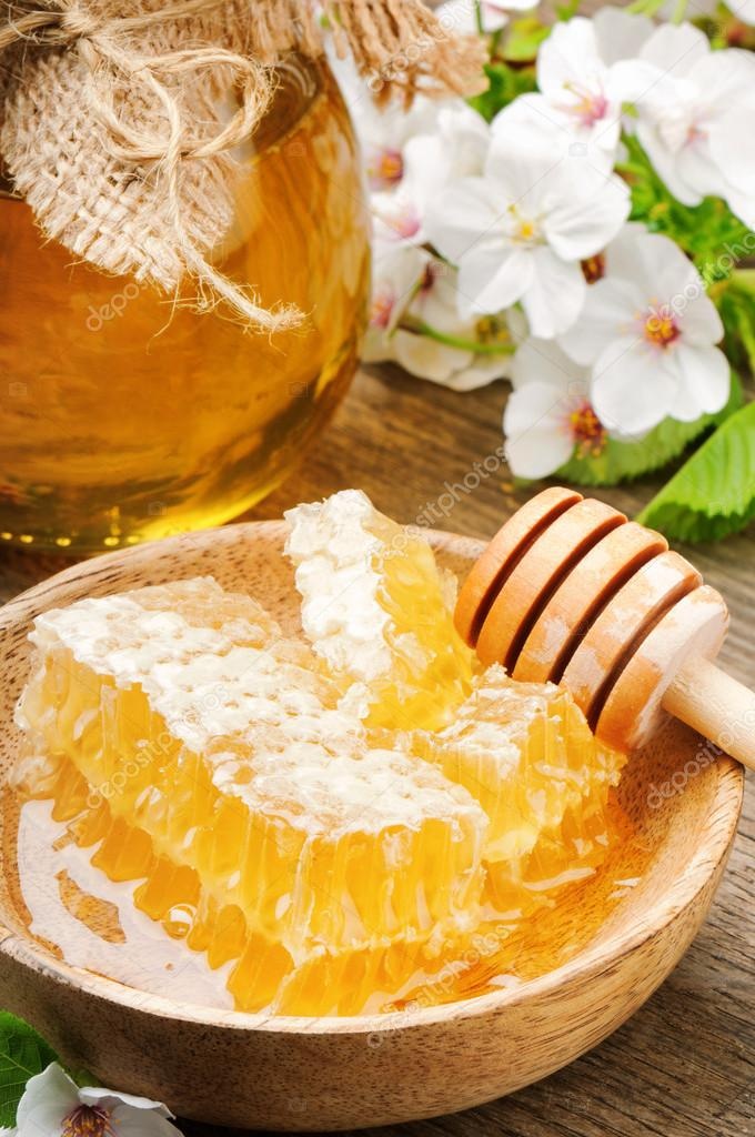 Glass honey pot and honey comb with flowers — Stock Photo #12727932