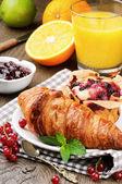 Breakfast with orange juice, fresh croissant and cake — Stock Photo