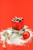 Christmas sleigh with gift on red background — Stock Photo