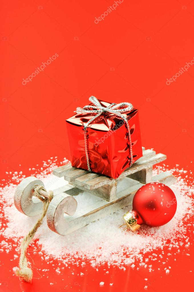 Christmas sleigh with gift and bauble on red background — Stockfoto #14531295