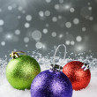 Colorful Christmas baubles on silver background - Stock Photo