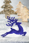 Christmas deer running in snowing forest — Stock Photo