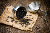 Metal tea infuser on wooden table — Stock Photo