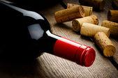 Bir şişe kırmızı şarap ve mantarlar — Stok fotoğraf