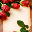 Frame with red roses and vintage paper - Stockfoto