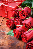Bouquet of red roses and gift box — Stock Photo