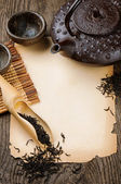 Frame with Asian teapot, dried black tea and vintage paper — Stock Photo