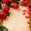 Foto Stock: Frame with red roses and vintage paper