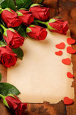 Frame with red roses and vintage paper — Stock Photo