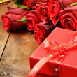 Valentine's setting with red roses, champagne and gift box - Stock Photo