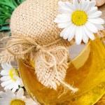 Pot of honey with daisies — Stock Photo