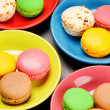 French macaroons in colorful plates - Stock Photo