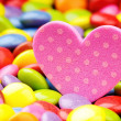 Pink heart and colorful smarties — Stock Photo