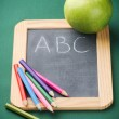 School supplies and green apple — Stock Photo