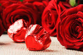 Chocolate hearts and red roses — Stock Photo