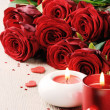 Red roses and candles in St Valentine's setting — Stock Photo