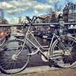 Old bicycle on bridge. Amsterdam cityscape — Stock Photo