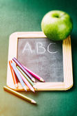 Colorful crayons on blackboard — Stock Photo