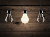 Unique bulb on wooden background — Stock Photo