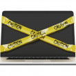 Laptop computer with yellow caution tape — Stock Photo