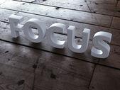 Word focus on wooden floor — Stock Photo