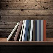 Pile of books on wooden shelf — Photo
