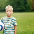 Boy standing and holding ball under his arm — Stock Photo