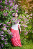 Beautiful young woman near the blooming lilac — Stok fotoğraf