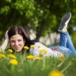 Young beautiful girl lying on a grass. Summer field with  flower — Stock Photo #49733061