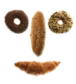 Funny face from doughnuts, bread roll and croissant isolated on white — Stock Photo
