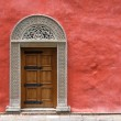 Carved Medieval Door in the Red Stucco Wall — Stock Photo #13396264