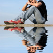 Stock Photo: Sitting Young Man with Reflection